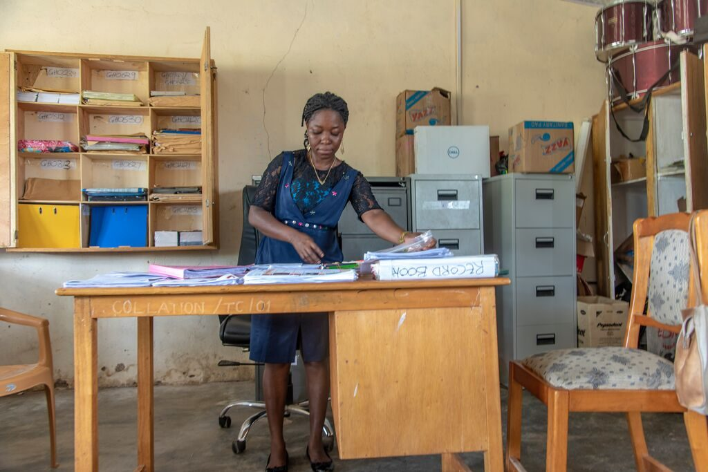 This is Emmanuella, a collation officer for the Tongu cluster. She receives all the cluster's letters and distributes them when the projects representatives come. She is standing behind a desk and is wearing a blue dress. There are filing cabinets in the background.