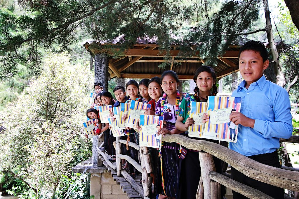 8 children are lined up on a bridge smiling, holding their workbooks.