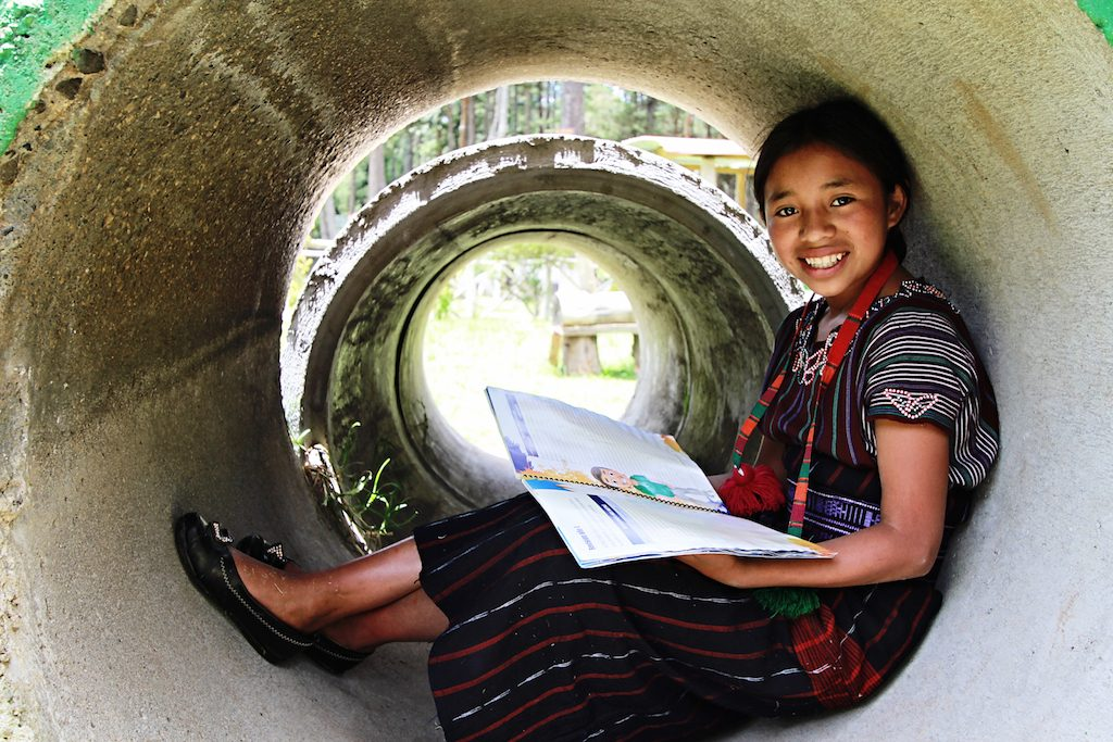 Little girl wearing a red scarf sits in a large concrete tube reading her book, smiling.