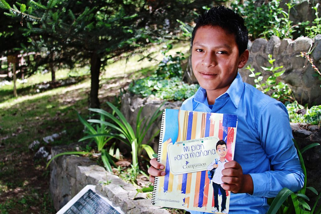 Young boy wearing a light blue button up shirt holds up his workbook sitting beside a garden.
