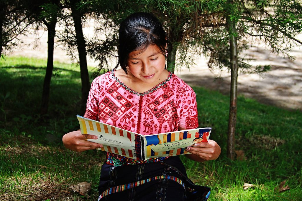 Little girl wearing a pin and read shirt sits in the grass and reads her workbook while grinning.