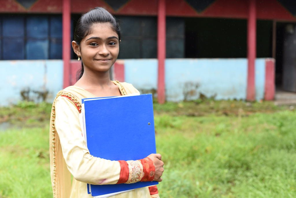 Teenage girl wearing yellow and red dress smiles in front of her Compassion centre, holding her workbook.