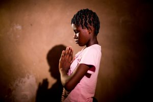 A girl in a pink shirt stands with her hands folded in front of her in prayer.