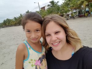 A woman smiles alongside a young girl.