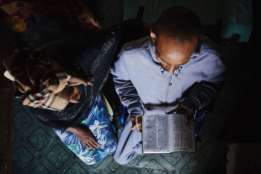 From overhead, a man and woman read the Bible together. The Bible is open on the man's lap as the woman looks over his left shoulder.