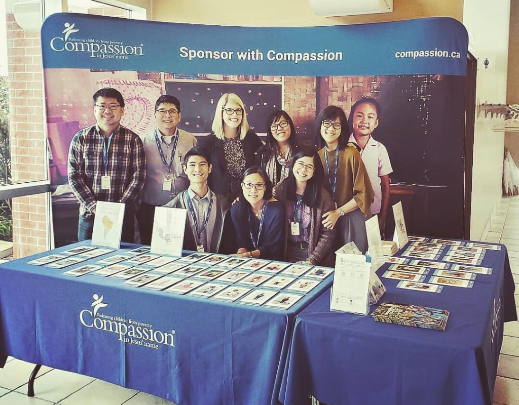 A group of people stand behind a table displaying Compassion information.