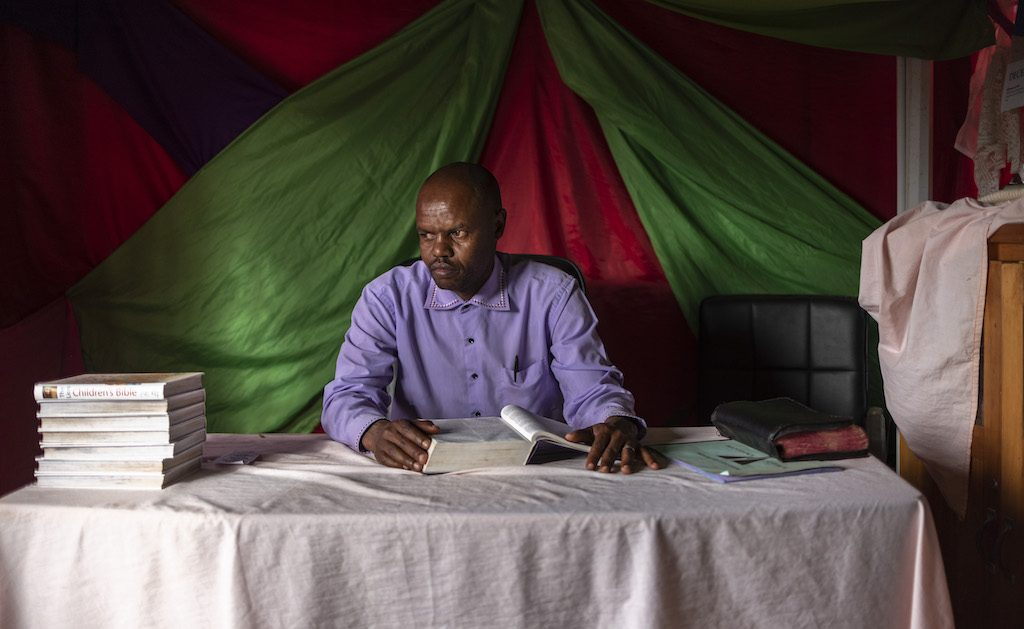 Pastor Richard sits at a table with a book open in front of him.