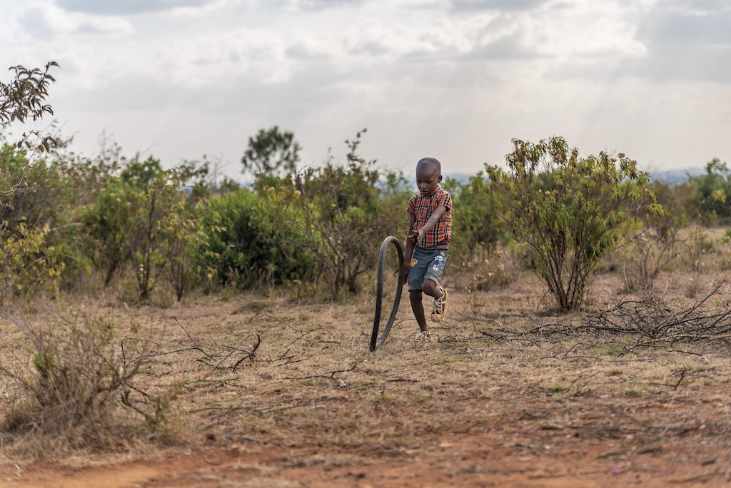 A child wearing a plaid shirt and denim shorts runs, playing with a tire.