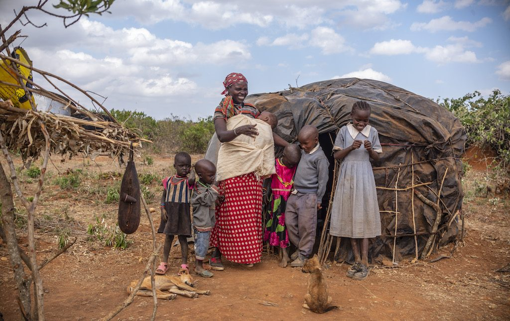 A family of seven people, a mother and six children, stands in front of a small black hut.