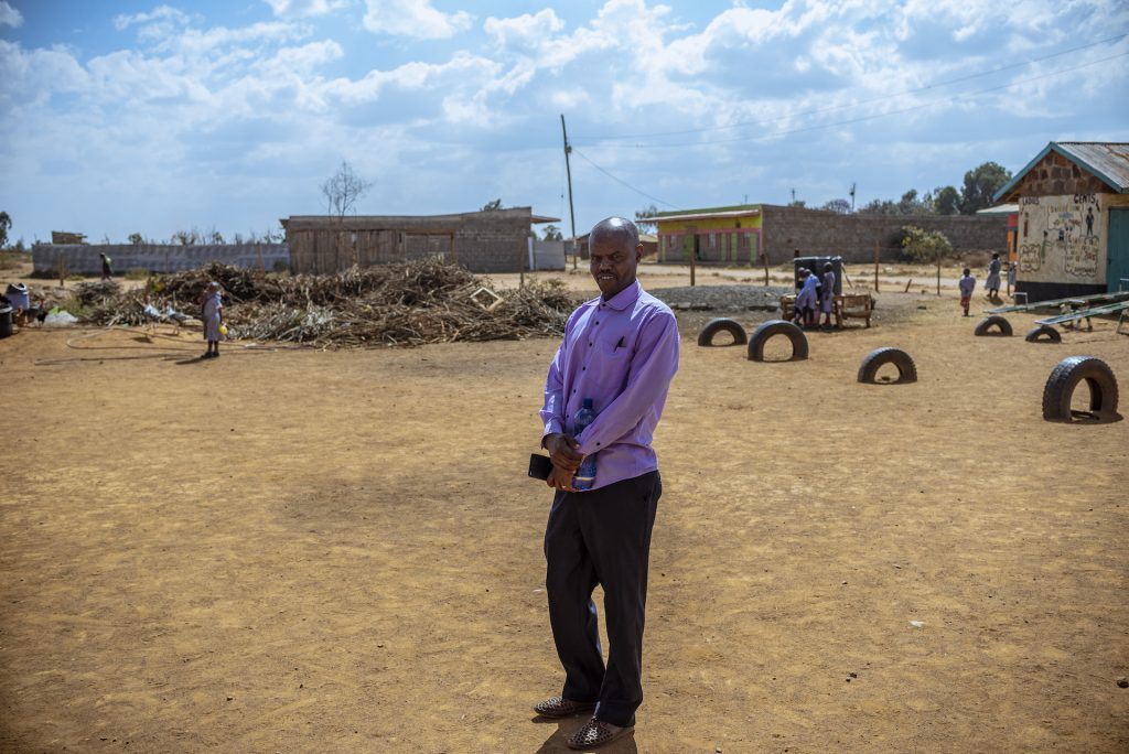 Pastor Richard stands in an open field in his community, wearing dark pants and a light purple shirt.