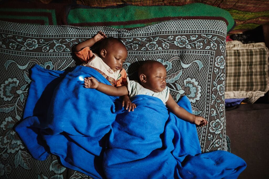 The twin baby girls sleep soundly with their arms spread wide covered in a blue blanket