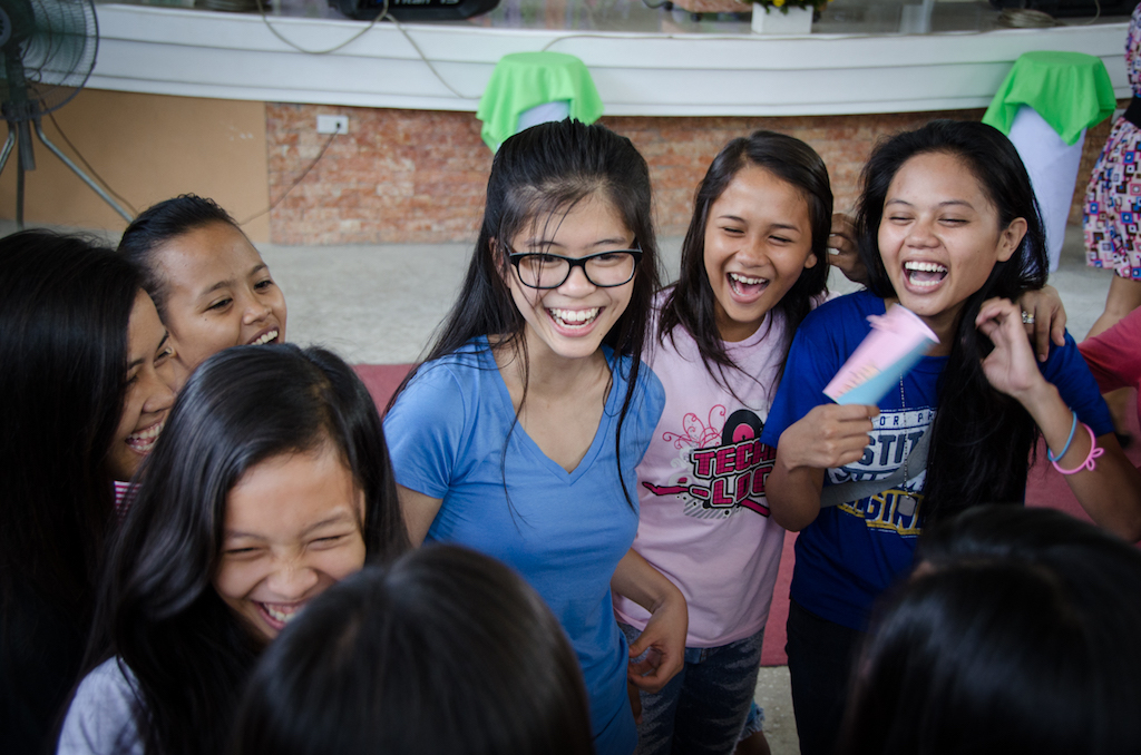A group of girls stand in a circle, laughing and chatting.