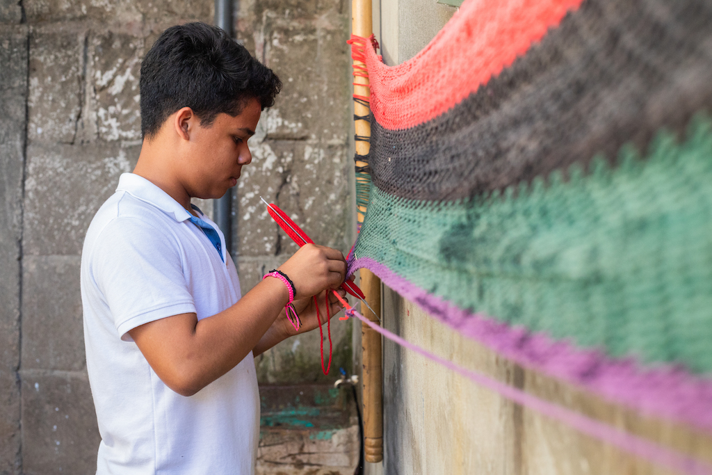 A boy in a white t-shirt woks on a red, black, green and purple hammock.