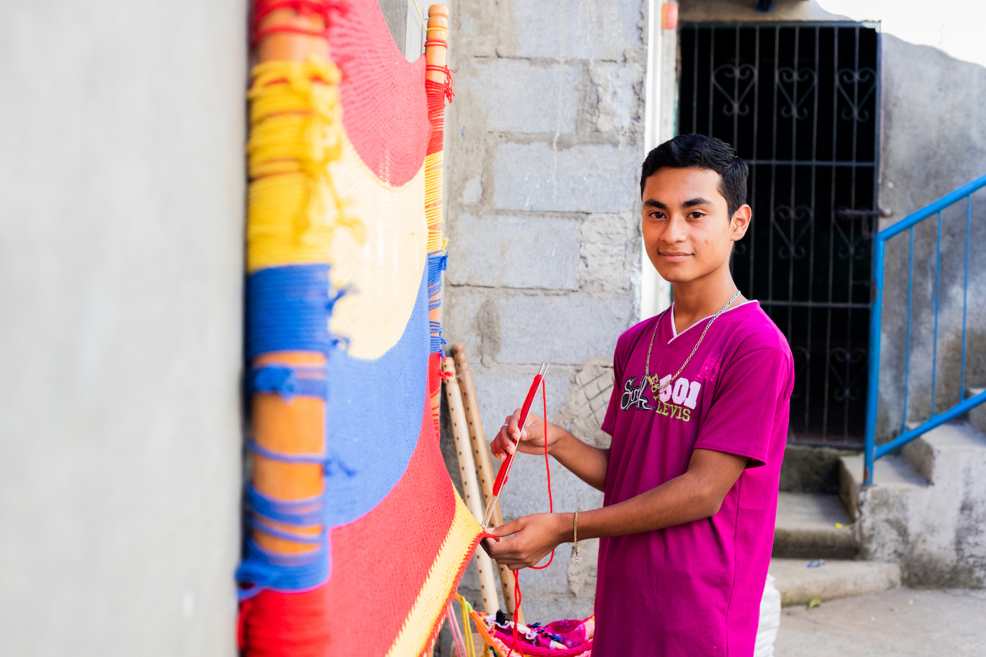 Ariel stands in a purple t-shirt, working on a red, yellow and blue hammock hanging on the wall in front of him.