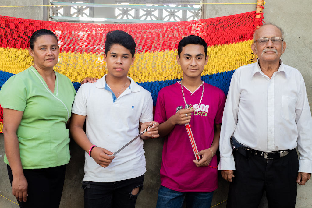 Two teenage boys stand with their tutor and instructor in front of a completed hammock hanging on a wall behind them.