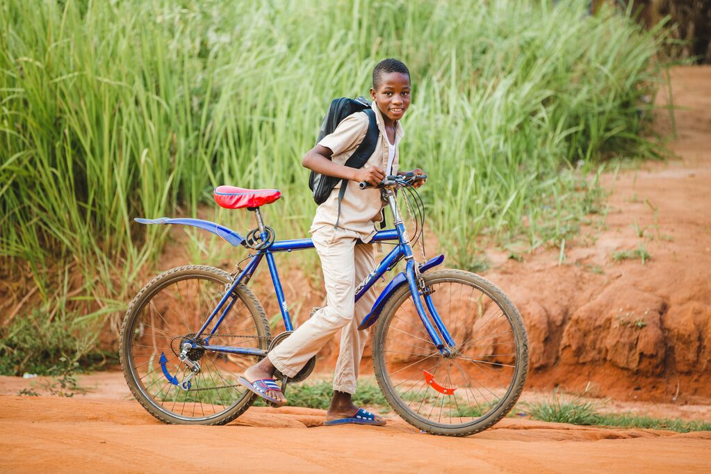 little boy wearing a black backpack and a blue bike on a dusty red road