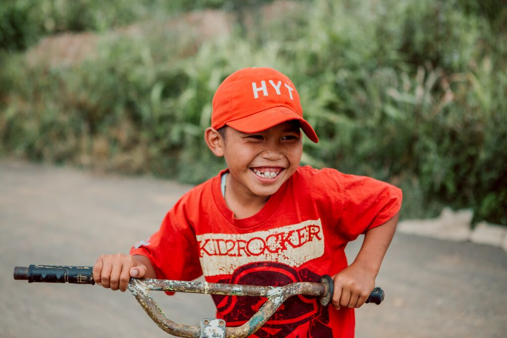 Little boy in an orange shirt and an orange hat grins on his bike