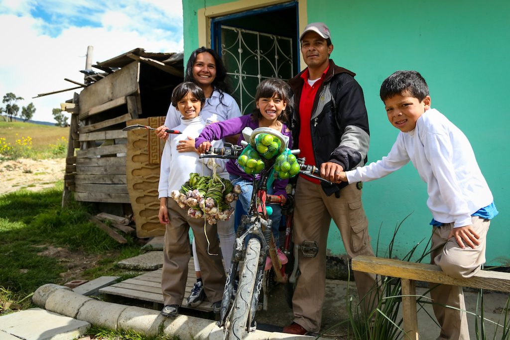 family of 5 smiles with fruit on their bicycle