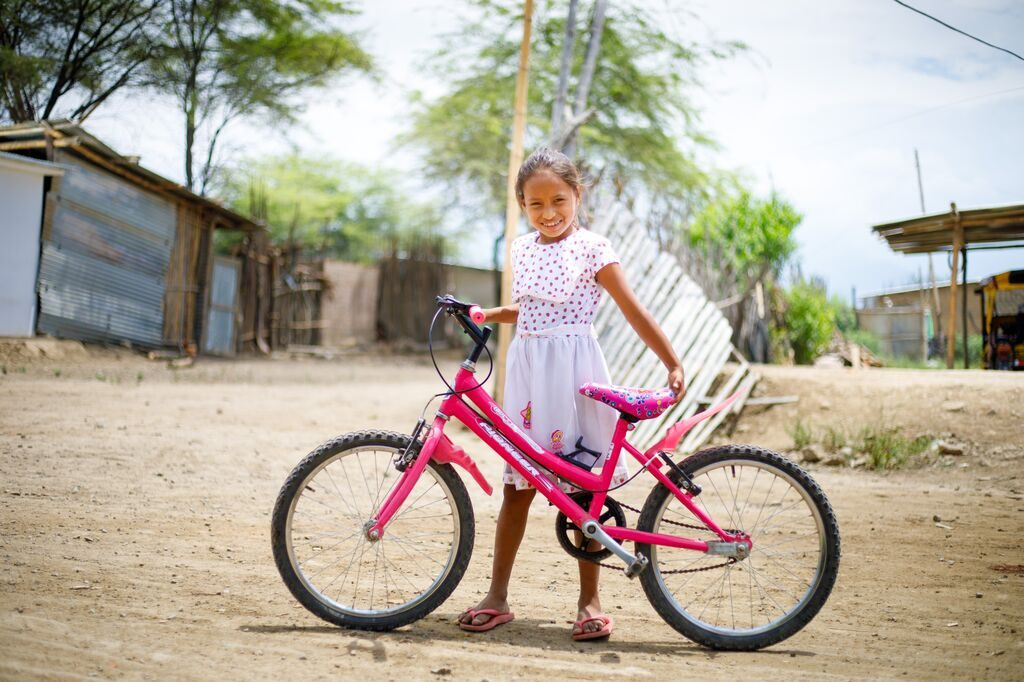 little girl holding a pink bike on a sunny day smiles