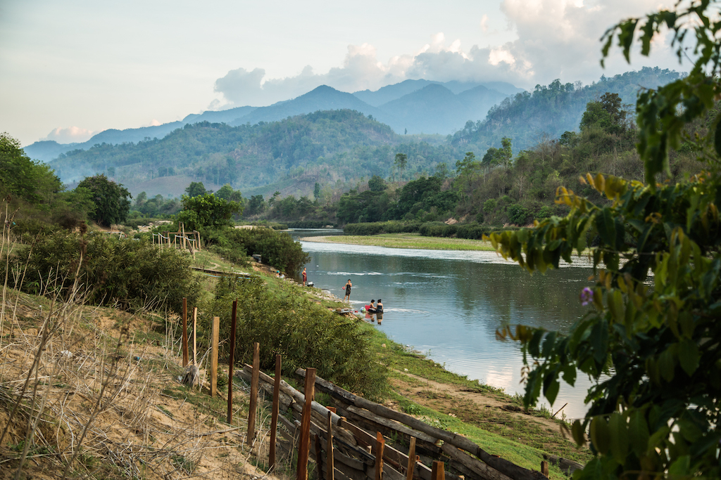 A landscape in rural Myanmar. There is a river in the foreground and green mountains behind.