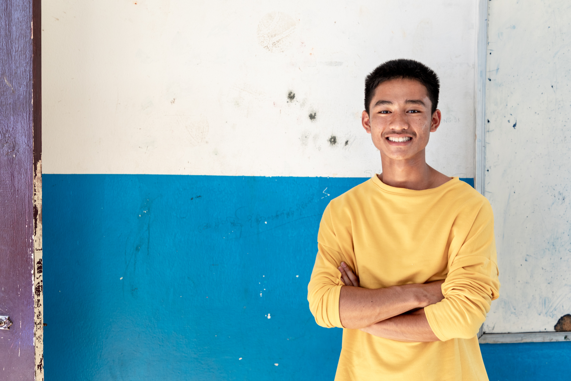 A portrait of 15-year-old Adun. He is looking at the camera, smiling with his arms crossed. He is wearing a mustard yellow crew-neck long sleeve shirt.