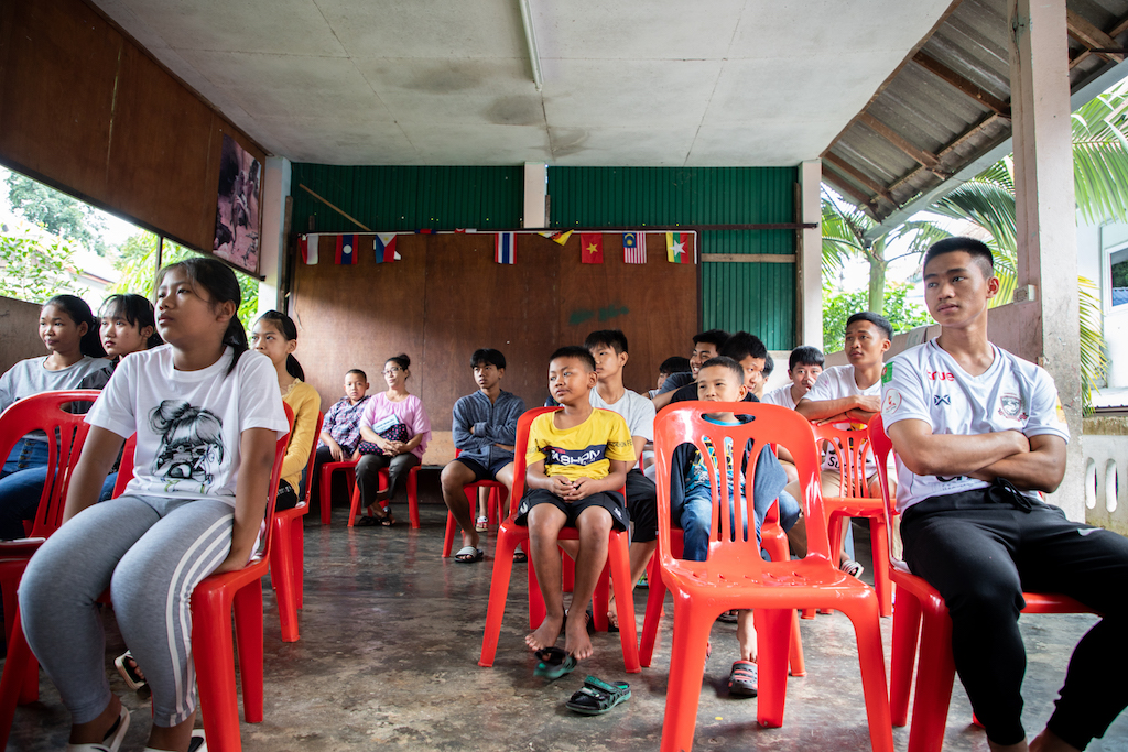 Thai children sit in red chairs in a classroom at the Compassion centre.