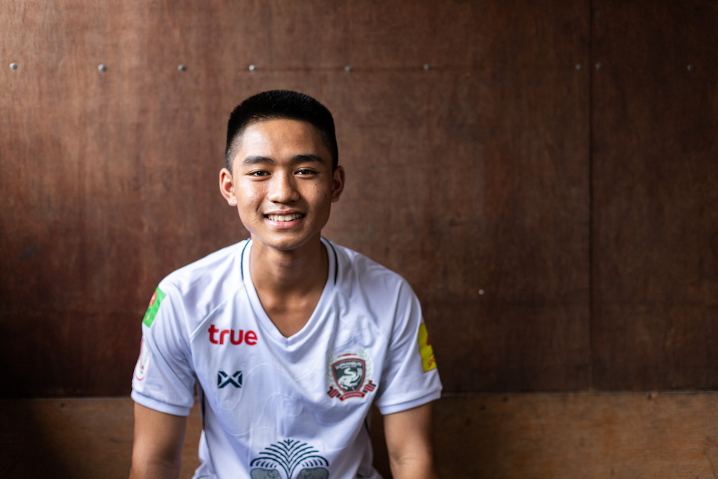 A heard and torso portrait of 15-year-old Adun. He is wearing a white football jersey and looking and smiling straight at the camera.