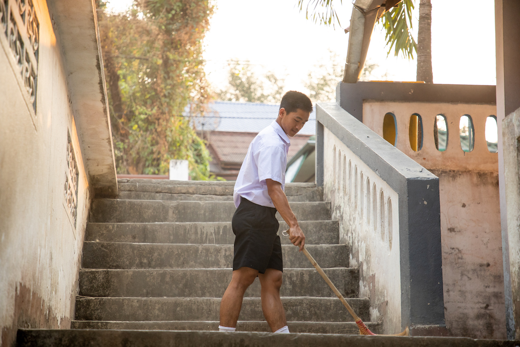 Adun, wearing a white short sleeve button-down shirt and dark shorts, sweeps some steps on the church hostel property with a broom.