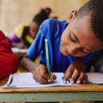 An Ethiopian boy in a blue shirt works on a letter to his sponsor. He is leaning over a wooden desk, writing with a green pencil.