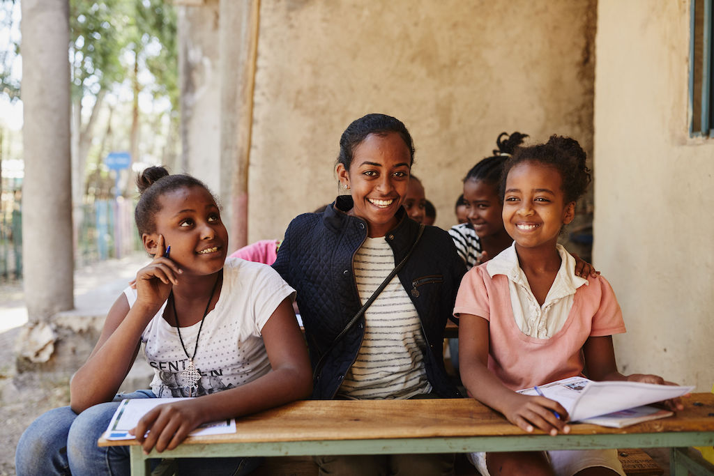 Betey sits at a long desk with two children in the Compassion program as they write letters. They are posing and smiling for the portrait. Betey is wearing a black jacket over a white and black striped t-shirt. The girl on the right is wearing a pink and white top, and the girl on her left is wearing a white t-shirt and blue jeans.