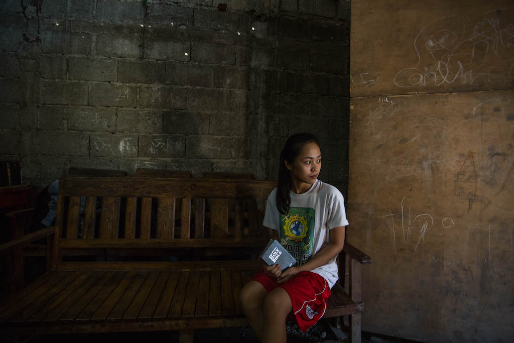 Maricris sits on a wooden bench, looking to the side. She wears a white tshirt and red shorts, and she is holding a Bible. Her long black hair is tied in a ponytail.