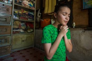 Bea is on her knees praying with folded hands.