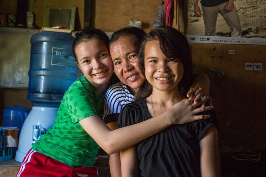 Bea with her sister and her mom hugging in their home