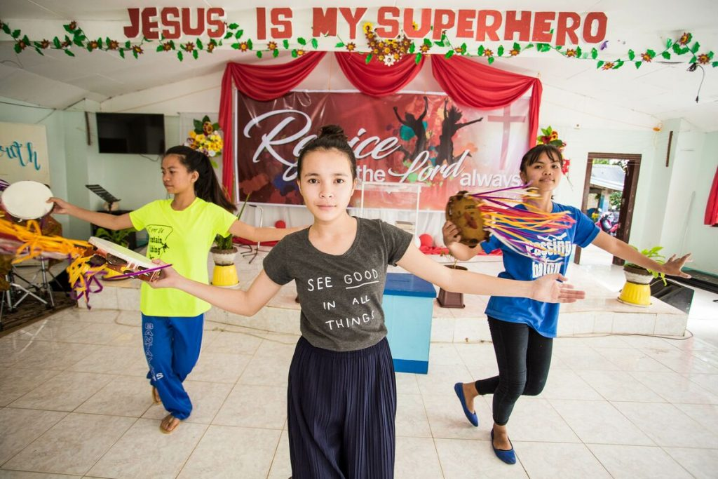 """Bea dances with a group of girls under a banner that says """"Jesus is my superhero"""""""