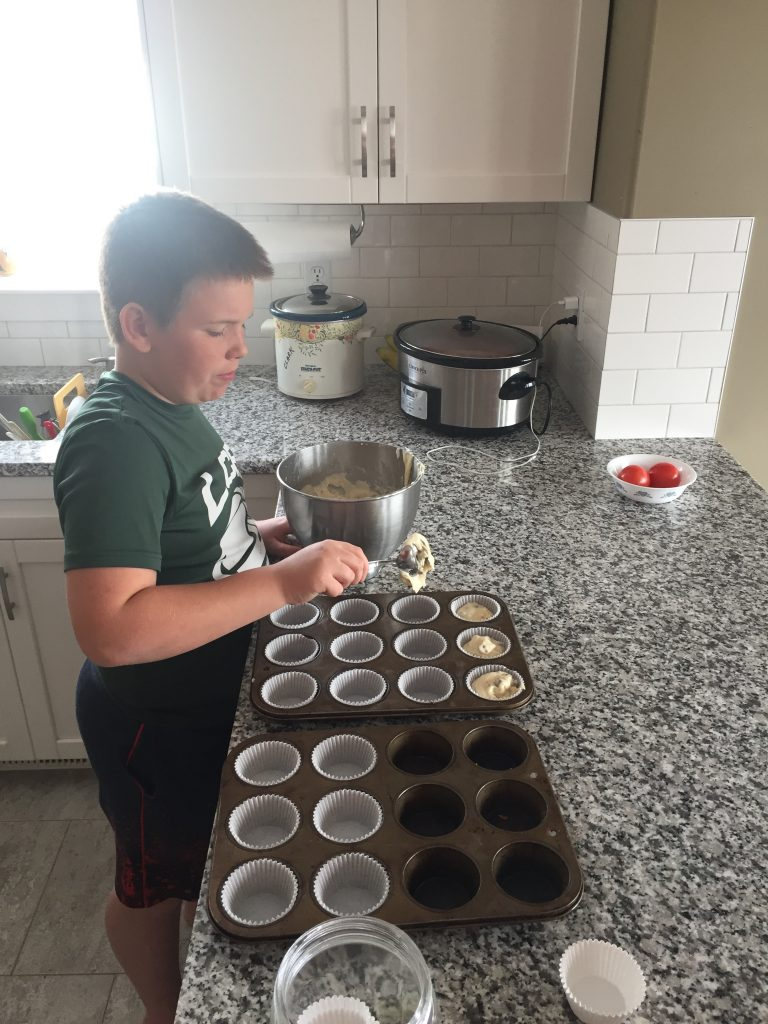 Jacob fills muffin tins with batter in his kitchen.