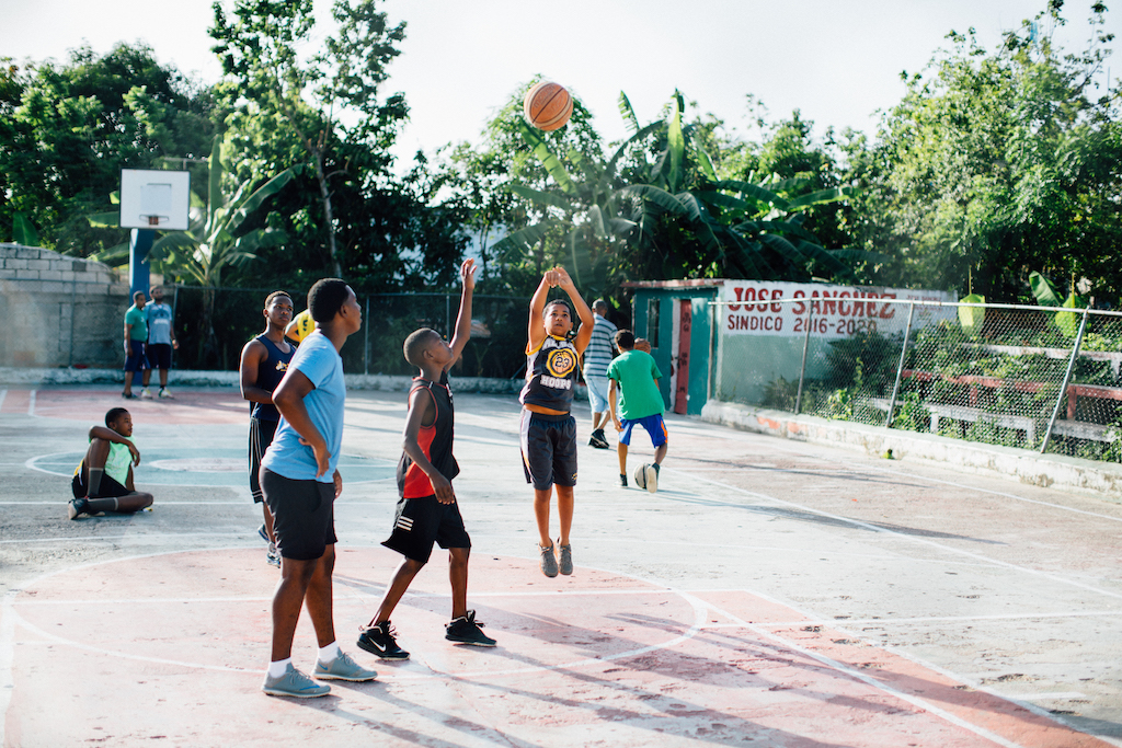 A group of boys play a game of basketball. One boy is shooting the ball while another has his hand up in attempt to block the shot.