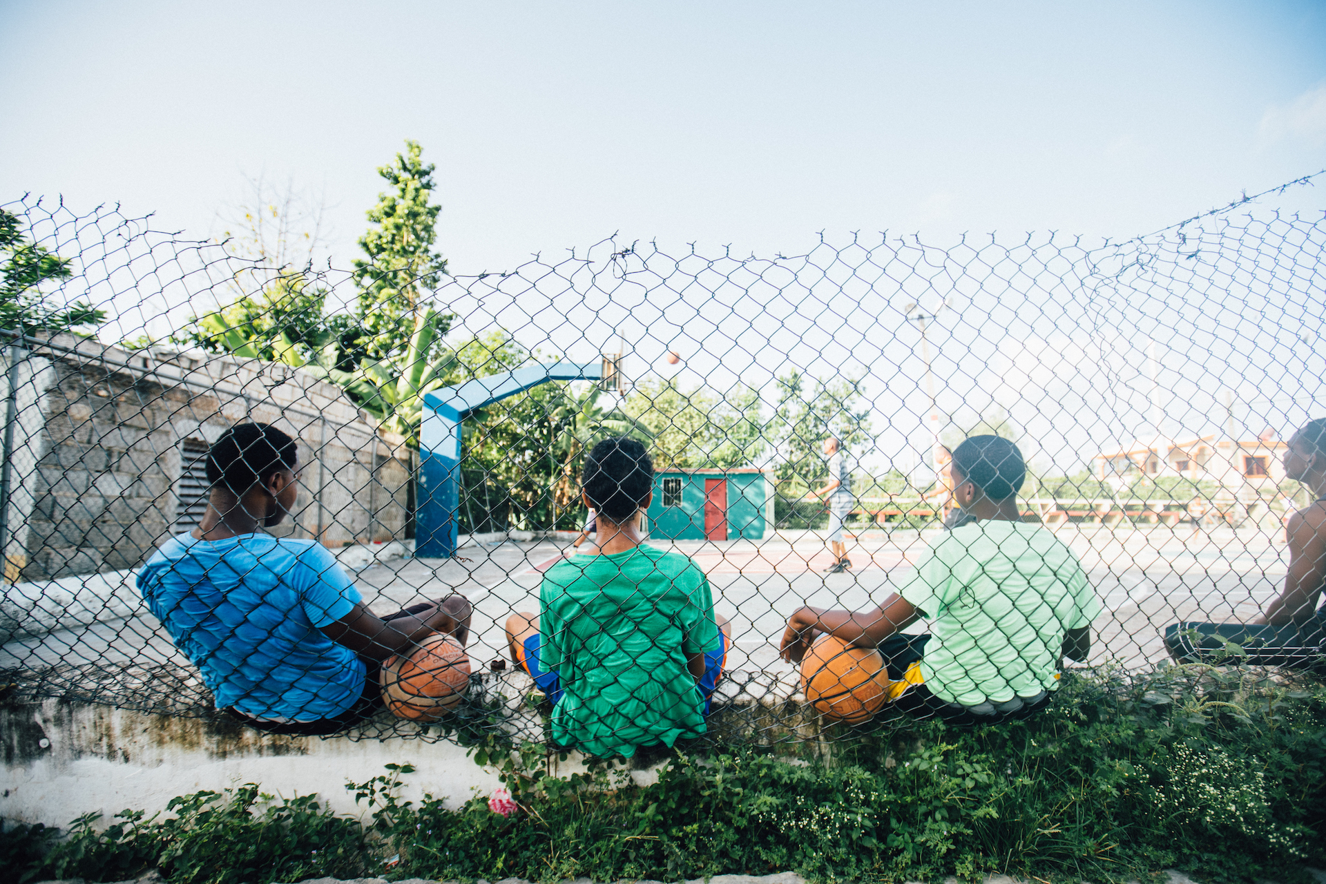 Three boys sit on the ground with their backs to the camera, leaning against a chain link fence. They are looking at a basketball court, holding basketballs.
