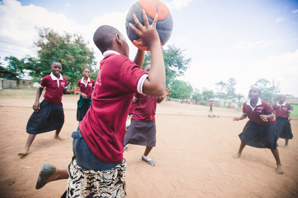 Girls in uniform are engaged in a game of basketball. One girl is preparing to pass the ball to another girl preparing to catch it.