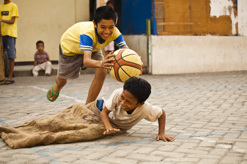 A boy lunges to tag another boy, who is sitting on the ground trying to dodge, with a basketball. They are smiling and laughing.
