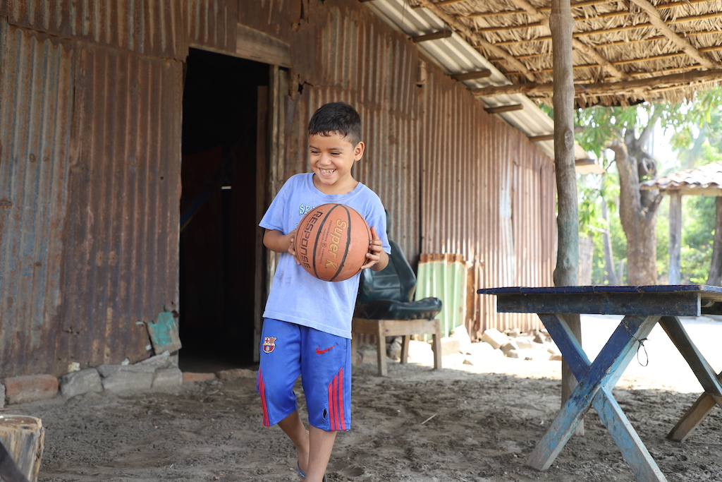 A boy in a blue t-shit and blue and red basketball shorts holds a basketball in both hands while walking outside his home.