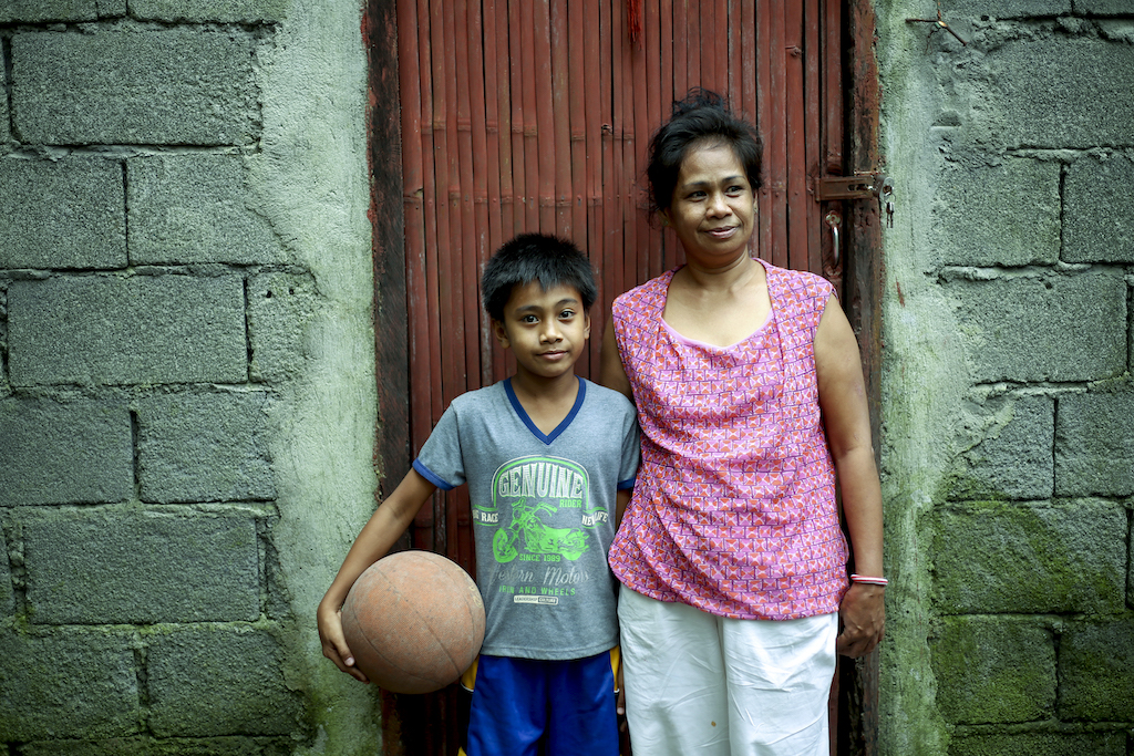 A woman in a pink shirt and a boy in a grey t-shirt stand in front of a brown door to a cinderblock home. The boy is holding a basketball on his hip.