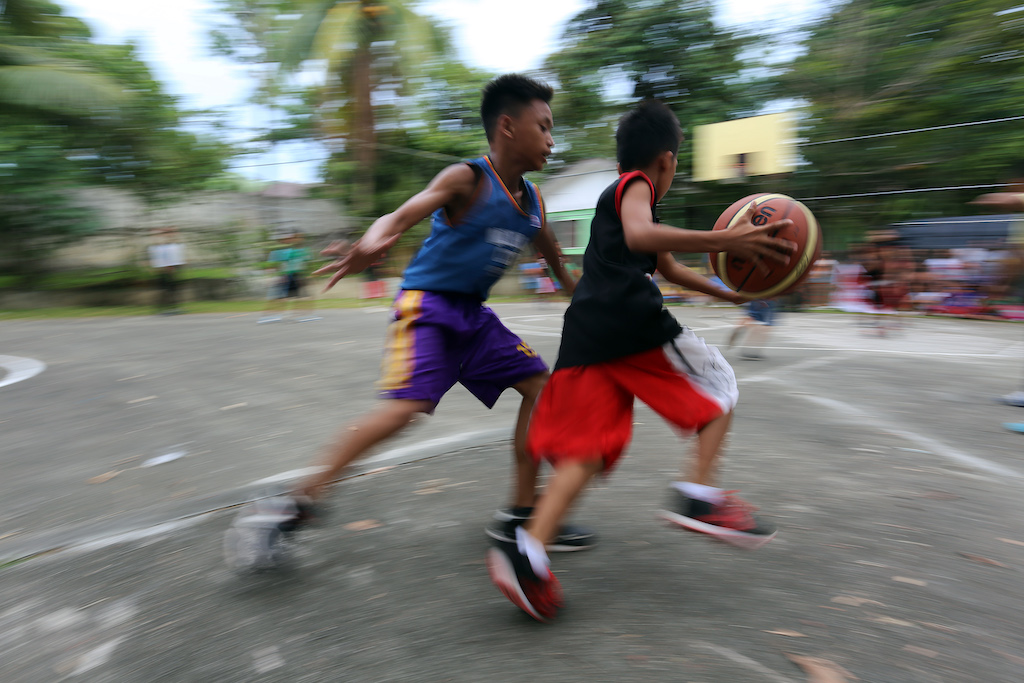 Two boys on opposite teams playing basketball. One boy is dribbling while the other defends.