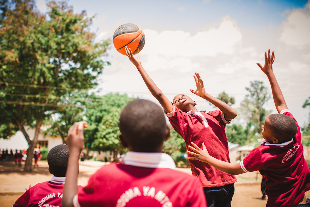 A boy jumps to reach for a basketball, amongst a crowd of other boys engaged in the game.