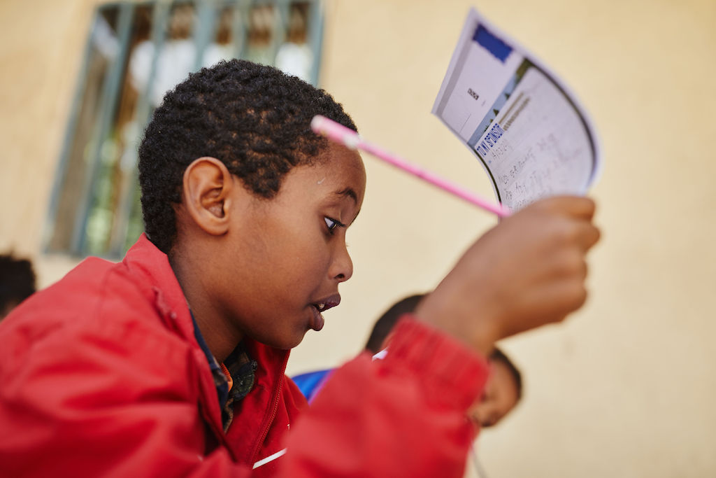 While working on a letter to his sponsor, Bemnet holds it up in front of his face to read what he's written. He is wearing a red jacket and holding a pink pencil.