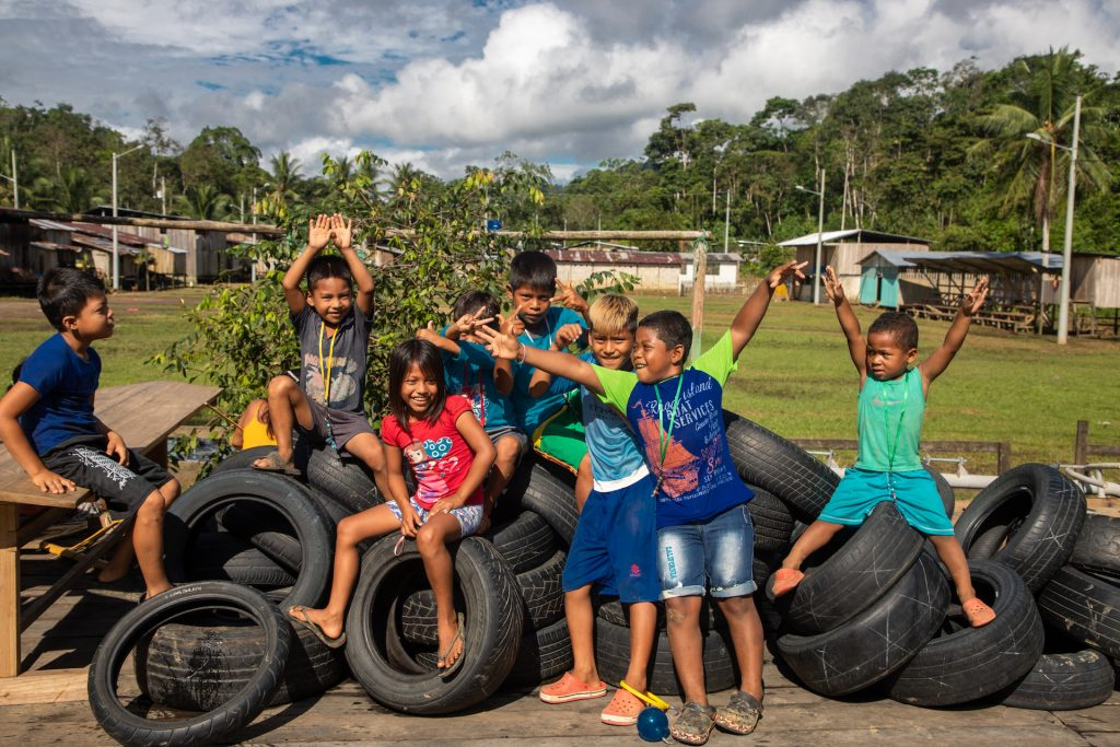 Chaci children play on a stack of tires