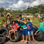 A group of Chachi children play on a pile of tires.
