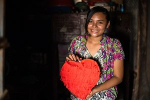 Estella poses with a heart pinata she made