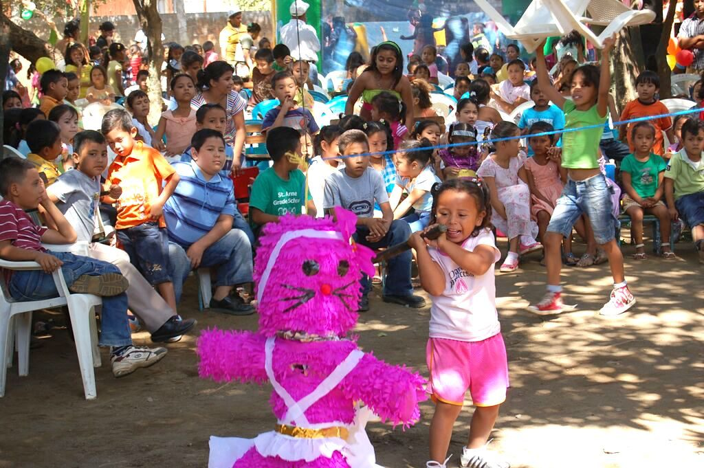 Little girl wearing pink shorts and surrounded by excited kids tries to hit the pink cat pinata