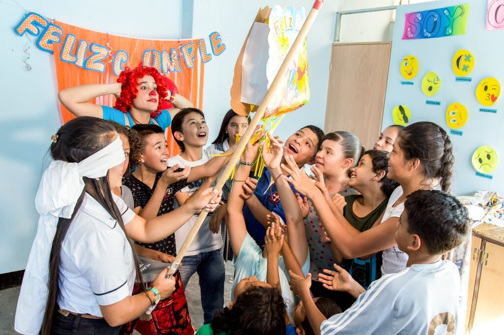 """Girl is blindfolded hitting the pinata that says """"Feliz Cumple"""" . There is a teacher dressed at a clown in the back looking excited."""