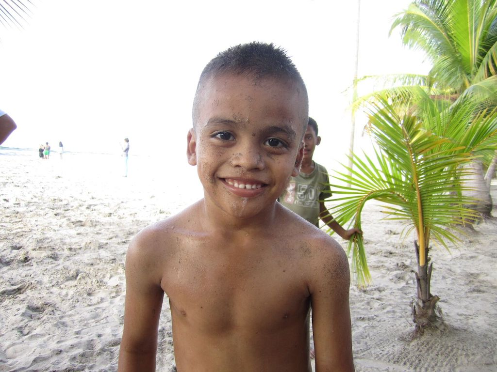 A shirtless boy covered in sand smiles at the camera on the beach.